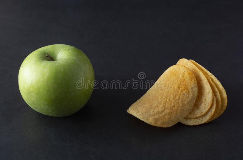 Food choise concept. Potatoe chips or green apple for snack. Top view, black background stock images