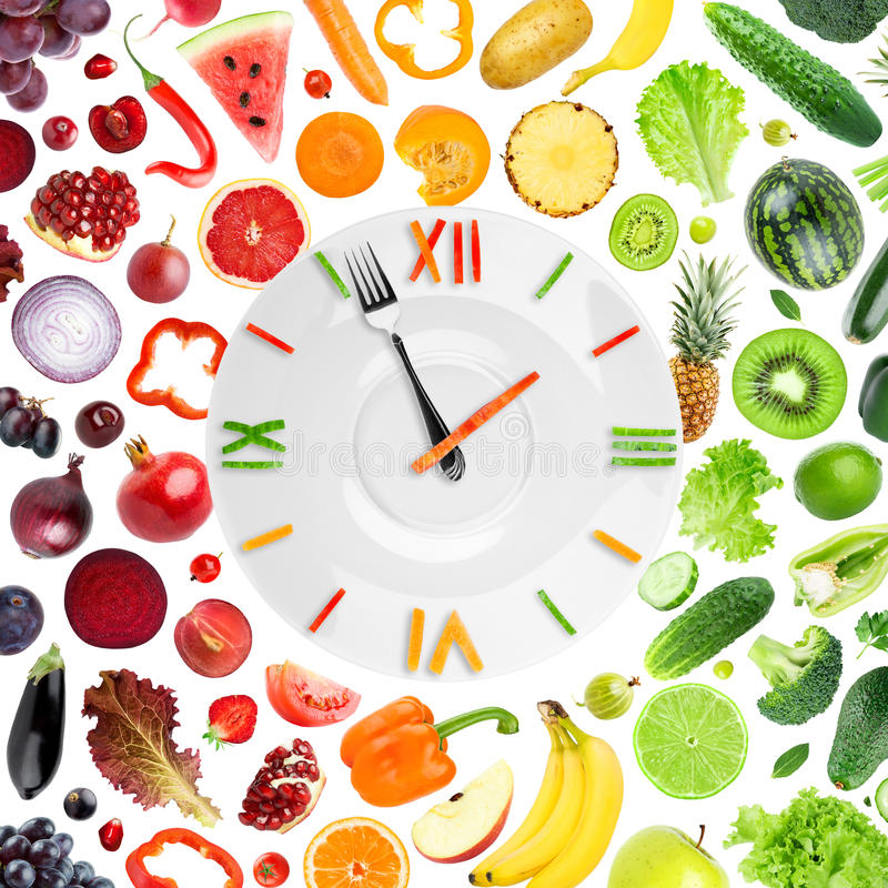Food clock with fruits and vegetables. On white background. Diet concept stock images