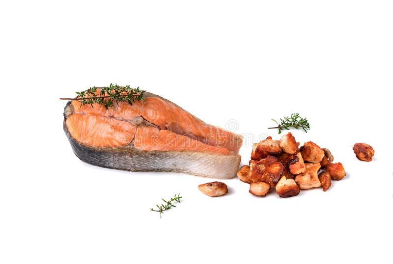 Food composition, grilled salmon steak, meat cut into small pieces with rosemary and black pepper isolated on white background stock photography