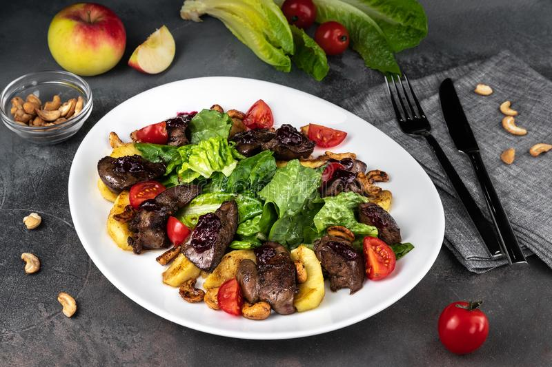 Food composition with liver salad and fried cashew. Arugula, tomato and potatoes on white plate on grey background close-up royalty free stock photo