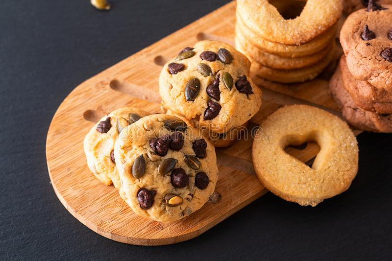 Food concept assortment of homemade sugar butter cookies on wooden board on black slate stone plate with copy space royalty free stock photo