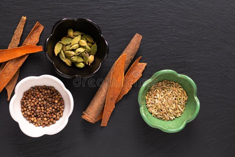 Food concept assortment Oriental spices cardamom pods, coriander seeds, fennel and Cinnamon Cassia Bark Sticks on black slate royalty free stock photos
