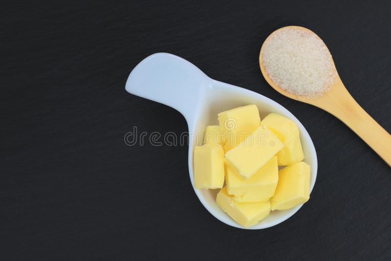 Food concept Butter in white cup and sugar in wood spoon on black slate plate. Butter in white cup and sugar in wood spoon on black slate plate with copy space stock photos