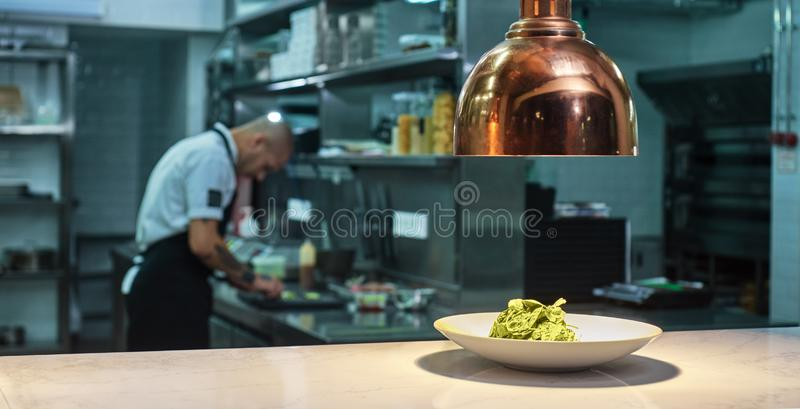 Food concept. Close up of fresh green salad on the plate standing on the table under the light with working chef on the. Background. Restaurant kitchen royalty free stock image