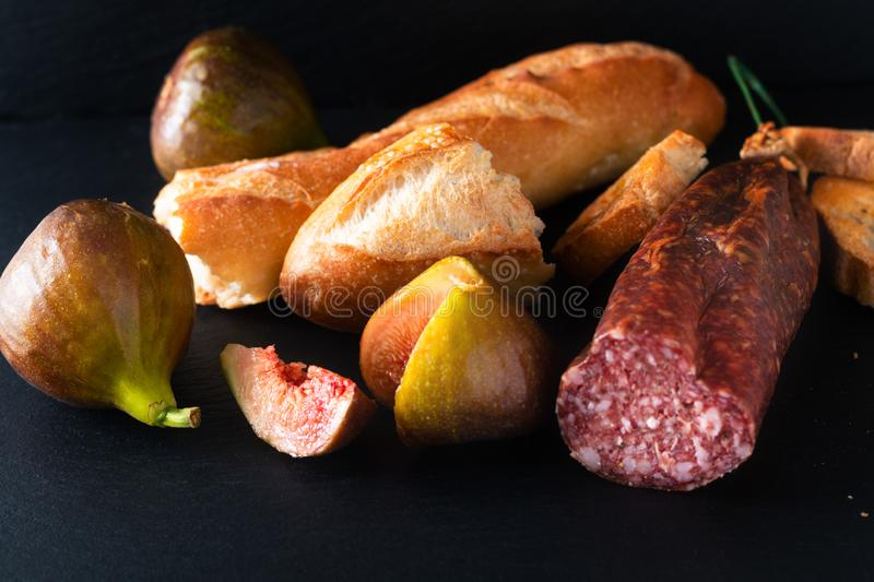 Food concept dried cured sausage on black slate board with copy space royalty free stock images