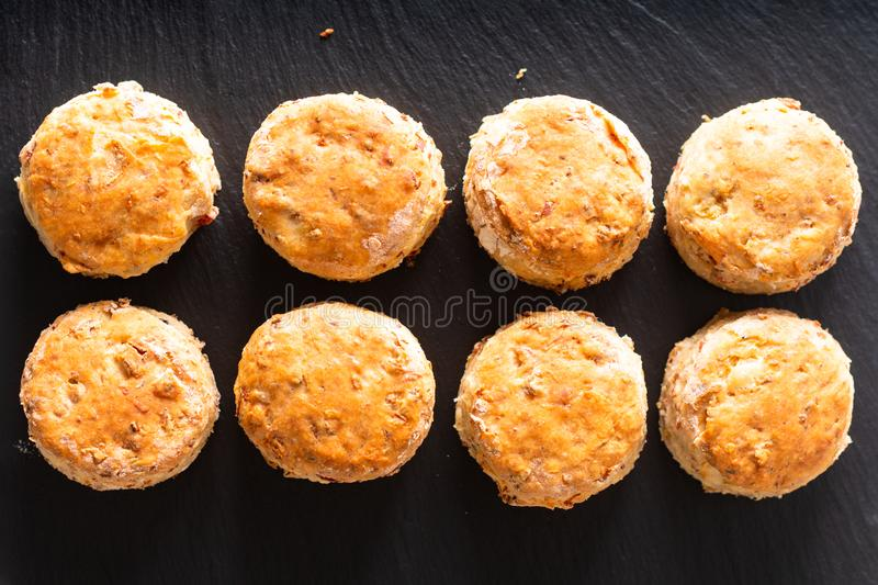 Food concept Fresh baked Homemade buttery, salty Ham and cheese scones on black background royalty free stock photo