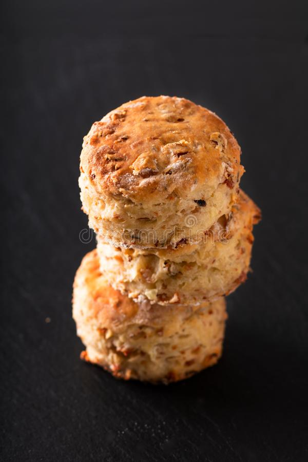 Food concept Fresh baked Homemade buttery, salty Ham and cheese scones on black background royalty free stock photography