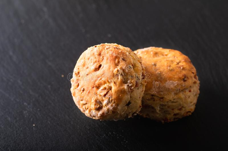 Food concept Fresh baked Homemade buttery, salty Ham and cheese scones on black background royalty free stock photos