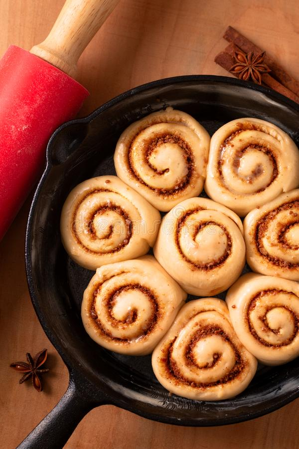Food concept puffy dough of homemade Cinnamon rolls raised before bake in skillet cast iron pan with copy space royalty free stock image