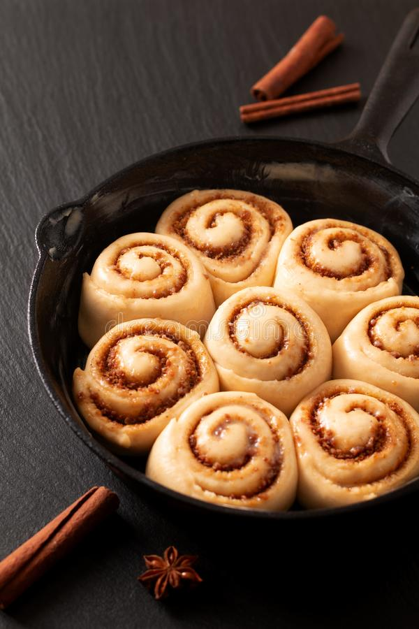 Food concept puffy dough of homemade Cinnamon rolls raised before bake in skillet cast iron pan with copy space stock images