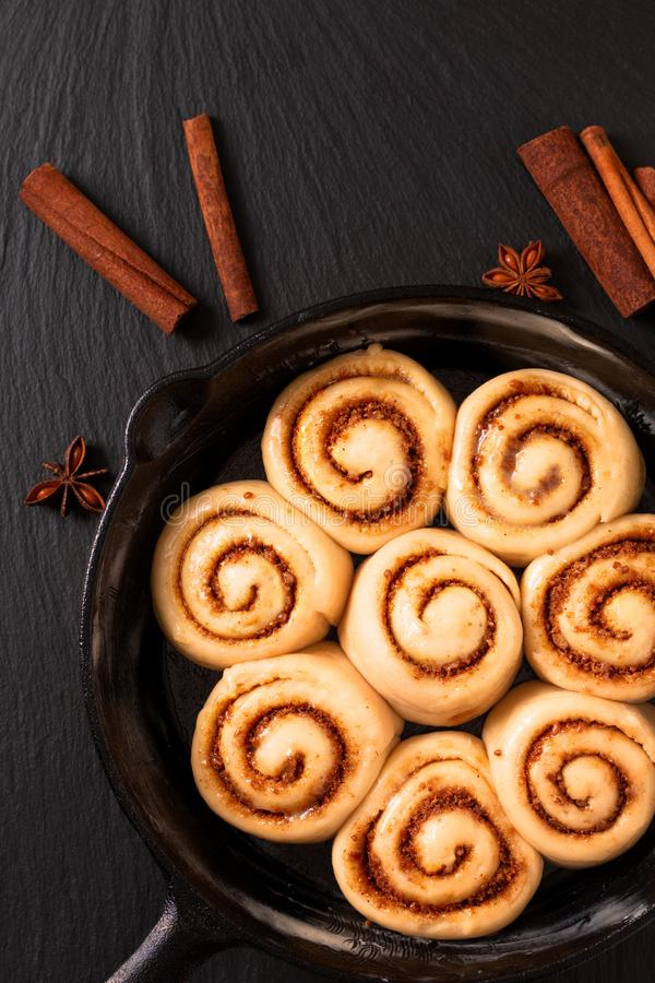 Food concept puffy dough of homemade Cinnamon rolls raised before bake in skillet cast iron pan with copy space stock photos