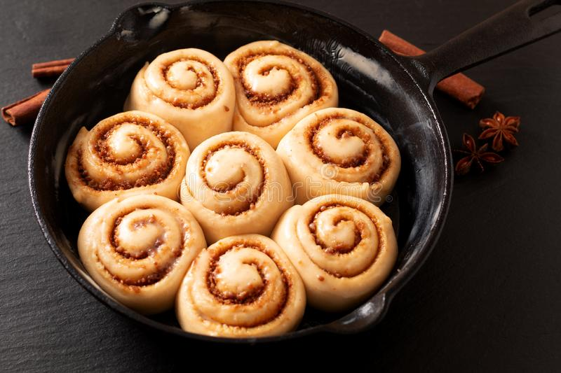 Food concept puffy dough of homemade Cinnamon rolls raised before bake in skillet cast iron pan with copy space royalty free stock photos