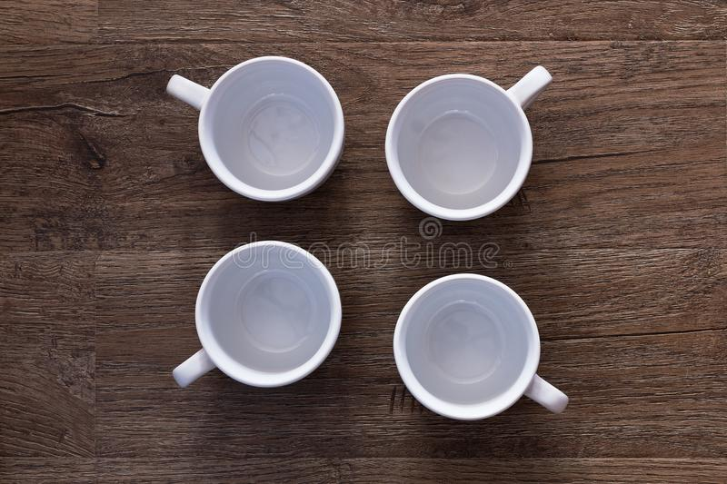 Food concept - top view of four white cups without saucers on gray brown wood table. Empty ceramic mugs. Food concept - top view of four white cups without royalty free stock photos