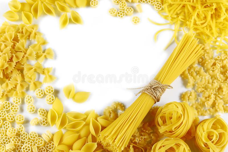 Food concept - various uncooked, raw Italian pasta on white background, top view, place for text, set royalty free stock photography