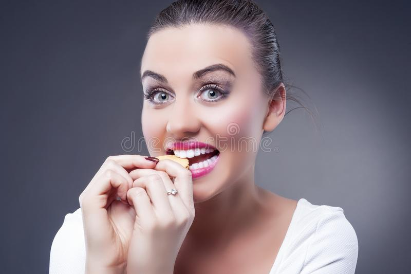 Food Concepts. Portrait of Young Smiling Happy Brunette Girl Bit stock images