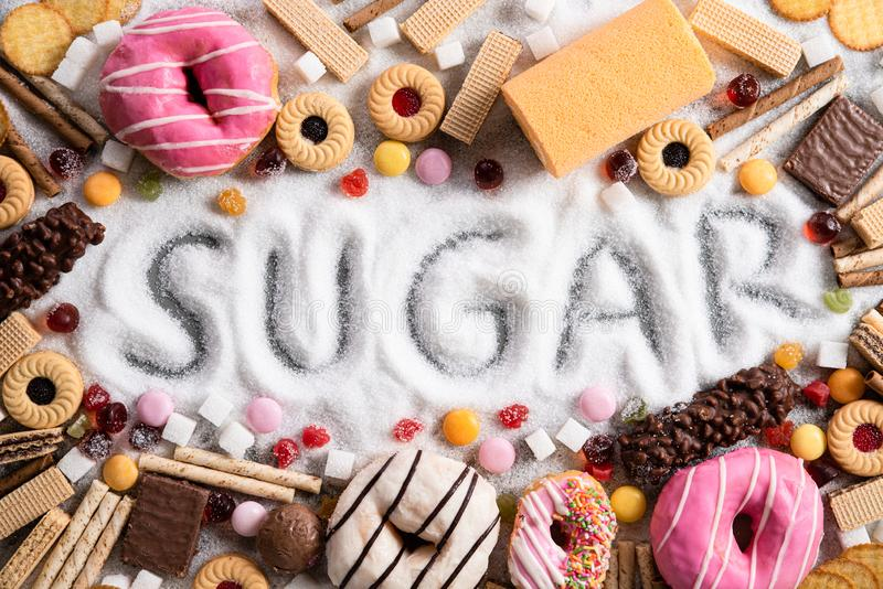 Food containing sugar. mix of sweet donuts, cakes and candy with sugar spread and written text in unhealthy nutrition, chocolate. Abuse and addiction concept royalty free stock photography