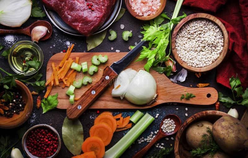 Food cooking background. Fresh organic vegetables, ingredients, spices and meat for warm autumn soup on vintage kitchen table with royalty free stock image