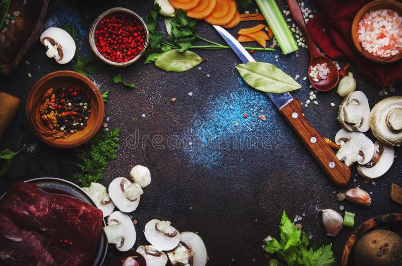 Food cooking background. Fresh organic vegetables, ingredients, spices and meat for warm autumn soup on vintage kitchen table with royalty free stock photos