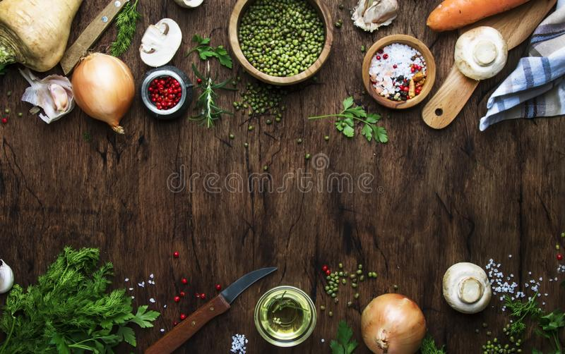 Food cooking background. Ingredients for prepare green lentils with vegetables, spices and herbs, wooden kitchen table background stock photography