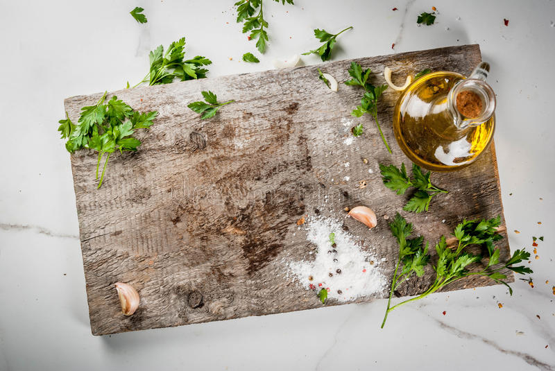 Food cooking background. Old cutting board on a white marble kitchen table. Olive oil, a knife, spices, salt, pepper, garlic, parsley. Top view copy space royalty free stock photos