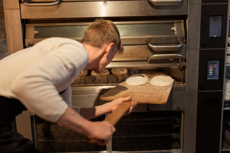 Baker putting dough into bread oven at bakery royalty free stock photos