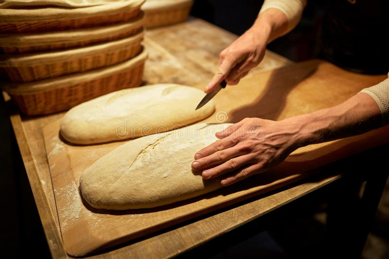 Baker making bread and cutting dough at bakery. Food cooking, baking and people concept - baker hands making bread and cutting dough with knife at bakery stock photos