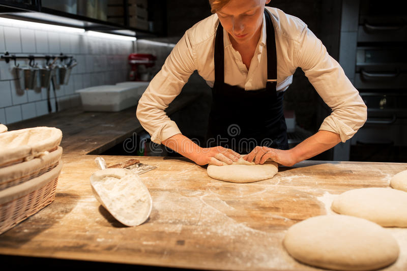 Chef or baker making dough at bakery royalty free stock photo