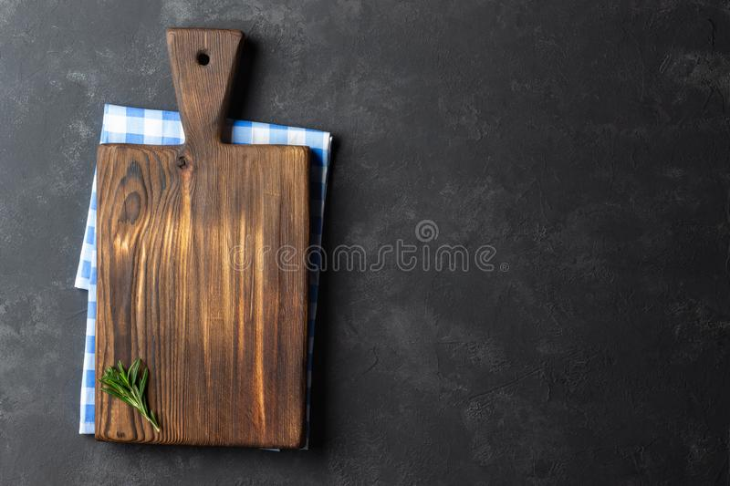 Food cooking concept. Vintage wooden kitchen board over napkin on dark stone background. Top view with copy space royalty free stock images