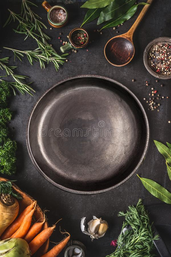 Food cooking and healthy eating background with empty dark rustic plate and fresh seasoning, spoon and vegetables ingredients royalty free stock photo