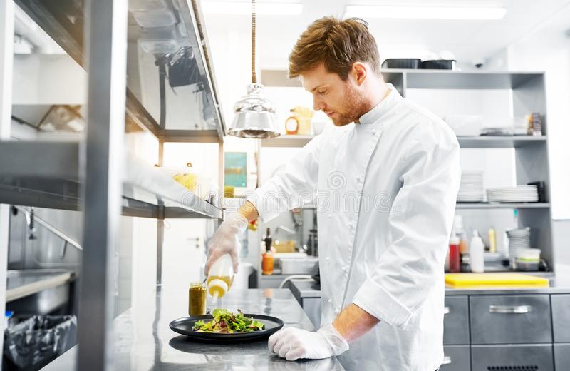 Happy male chef cooking food at restaurant kitchen. Food cooking, profession and people concept - happy male chef cook making vegetable salad at restaurant stock image