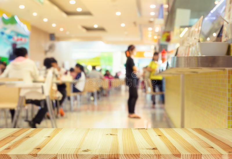 Food court blurred. Defocused or blurred photo of food court montage with wood table top use for background royalty free stock photo