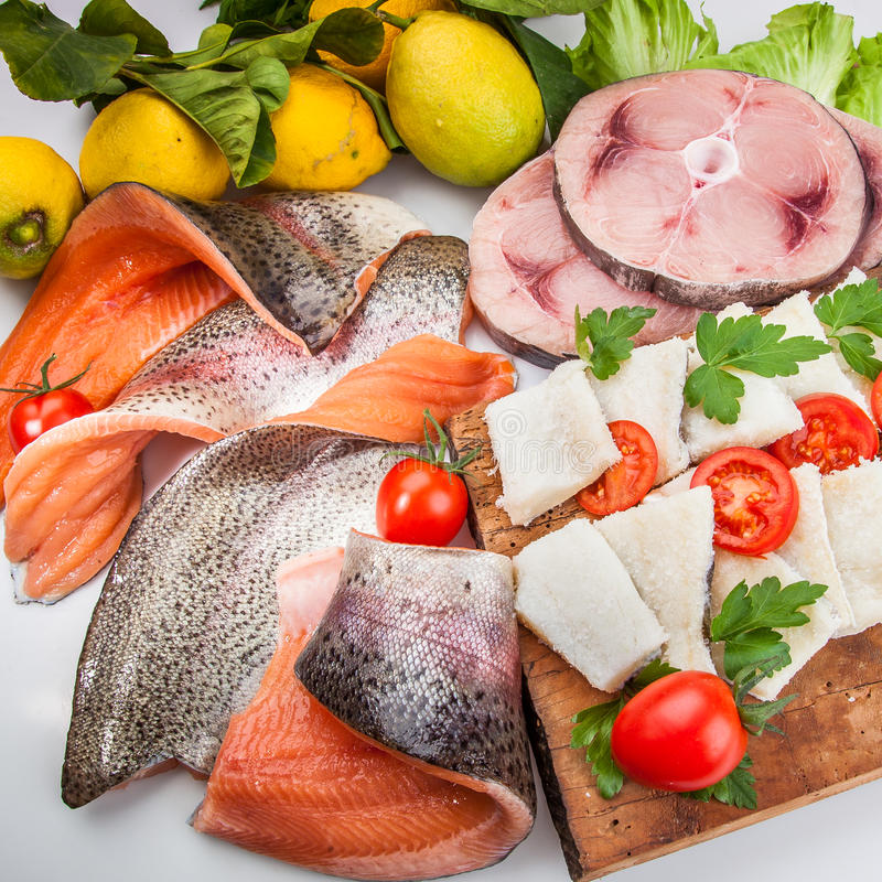 Food cousine fish composition, ingredient for eating. Fish composition with vegetables, salmon swordfish and cod with tomatoes lemon and parsley stock photography