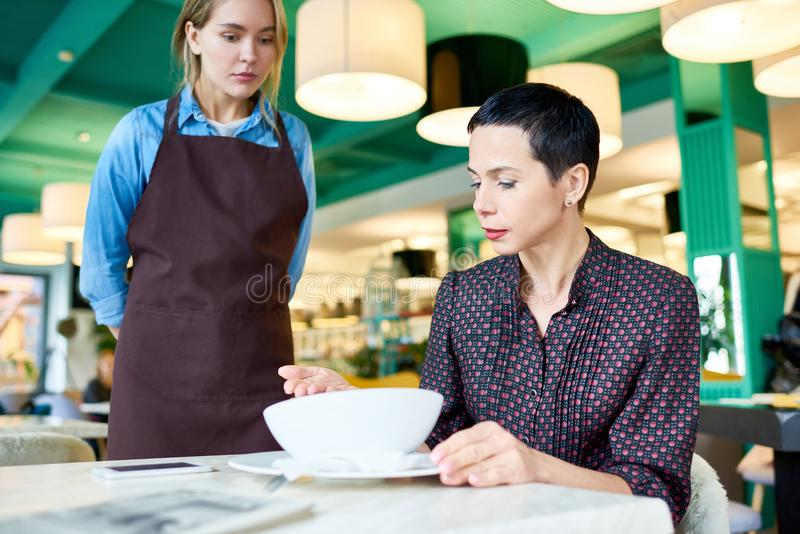 Food Critic. Portrait of elegant women complaining about food quality and taste to young waitress in cafe royalty free stock photography