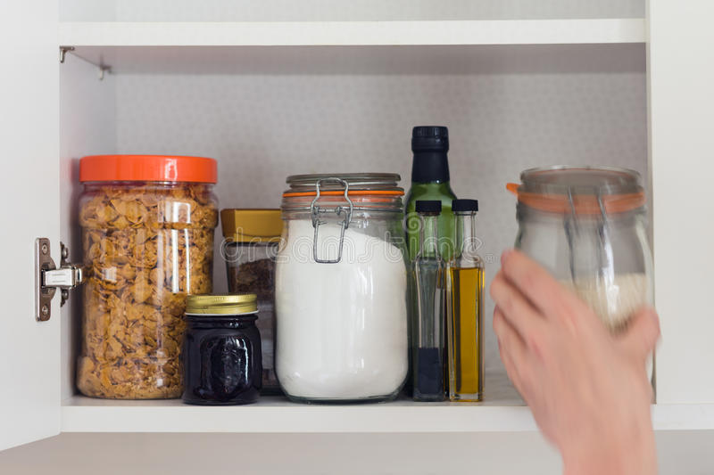 Food cupboard, pantry with jars, hand stock photos