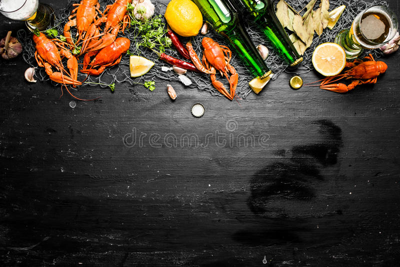 The food delicacies. Boiled crawfish with beer and spices. On a black chalkboard stock photo