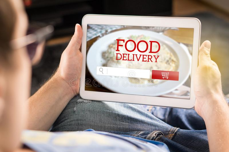 Food delivery app on tablet. Man using smart device at home to make an order from restaurant online. Imaginary application, website and internet store on stock image