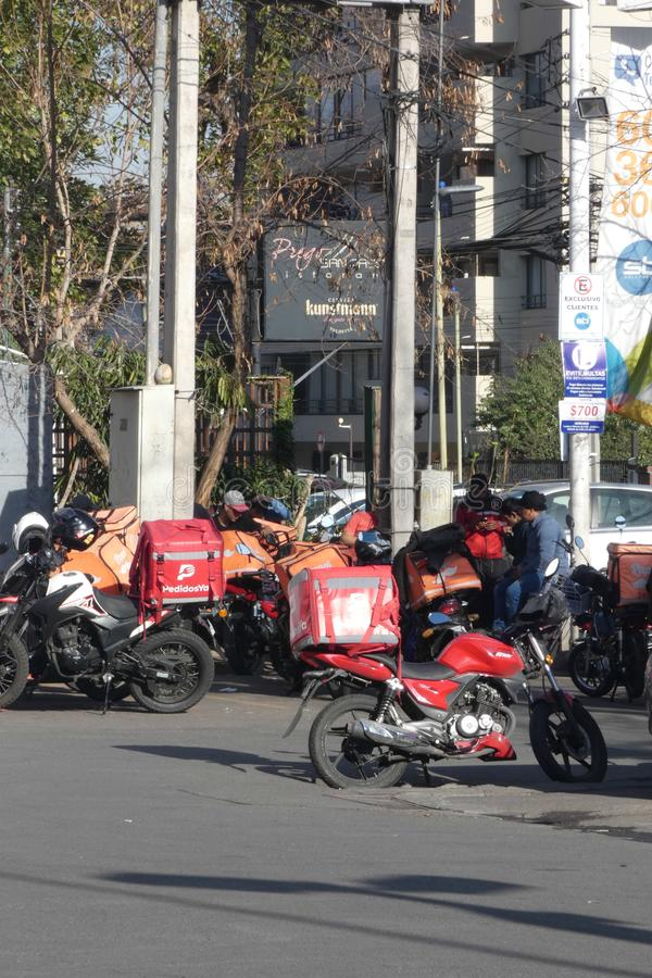 Food Delivery App Workers. Food delivery apps workers taking a break on a parking lot in Santiago, Chile royalty free stock photos