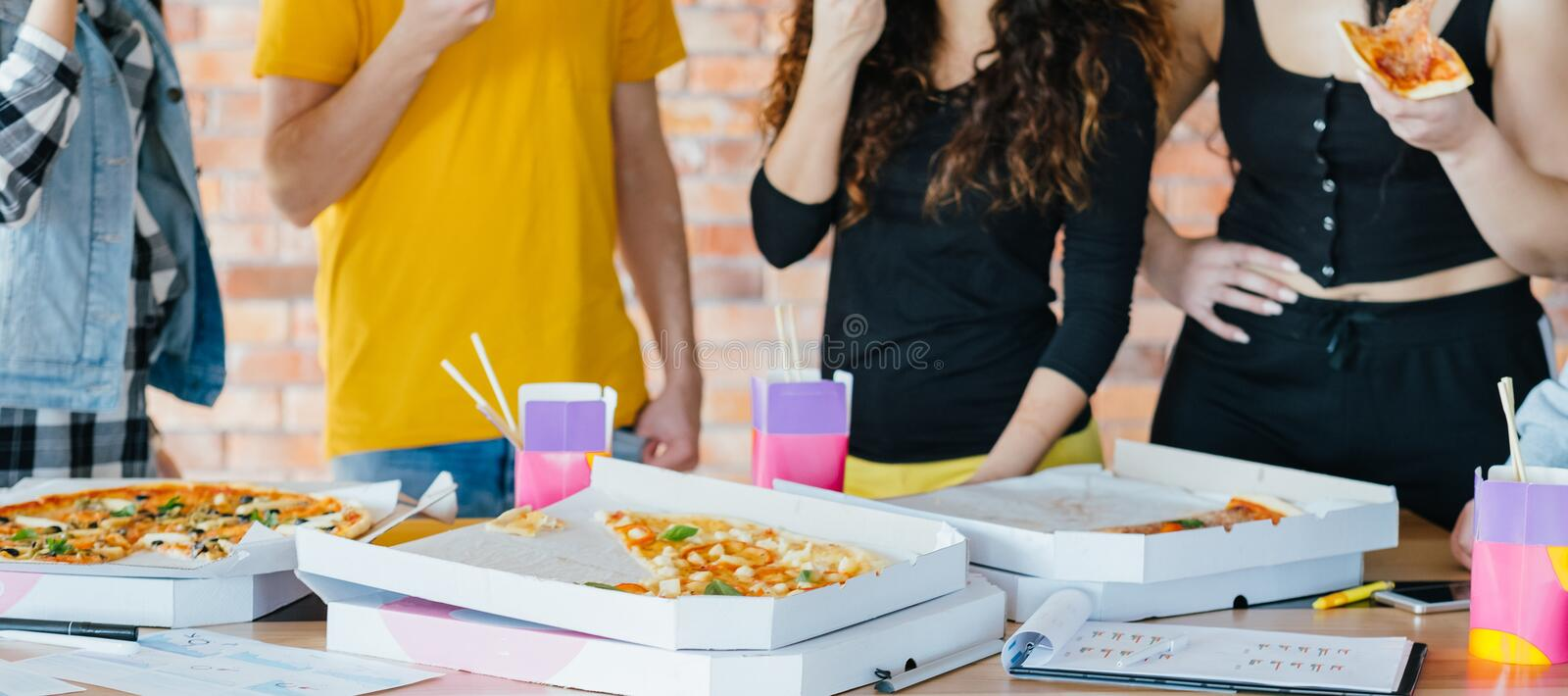 Food delivery business guys pizza takeout lunch. Food delivery for busy business guys. Pizza and takeout meal boxes. Cropped shot of men women eating. Lunch royalty free stock photography