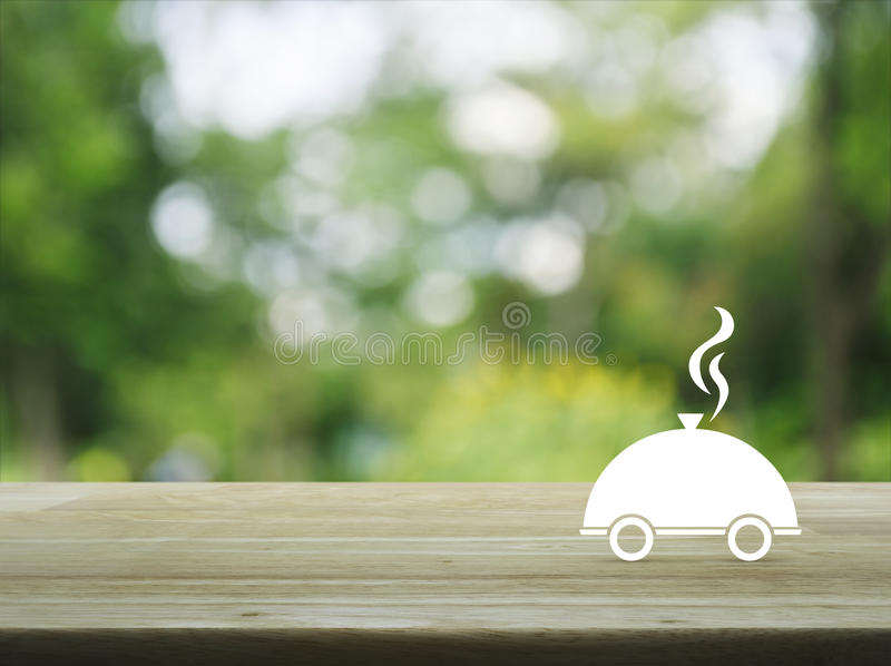 Food delivery concept. Restaurant cloche flat icon on wooden table over blur green tree background, Food delivery concept stock images