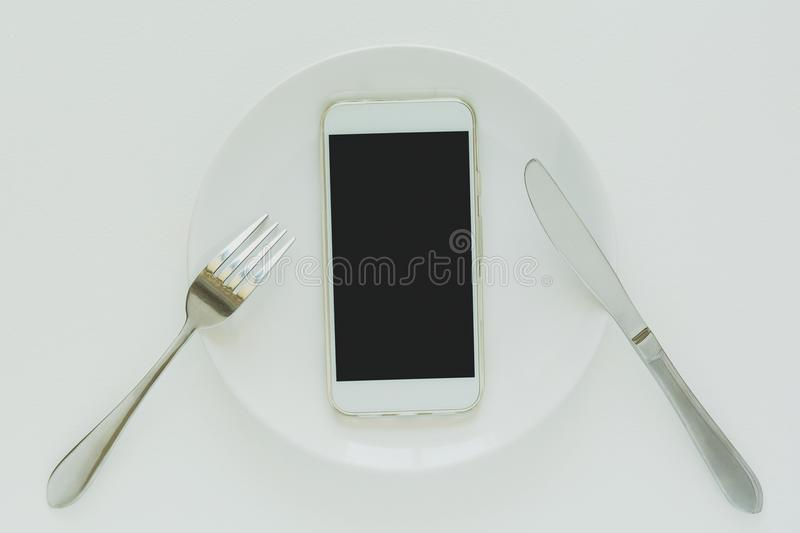 Food delivery concept. Top view on smartphone laying on plate stock photo