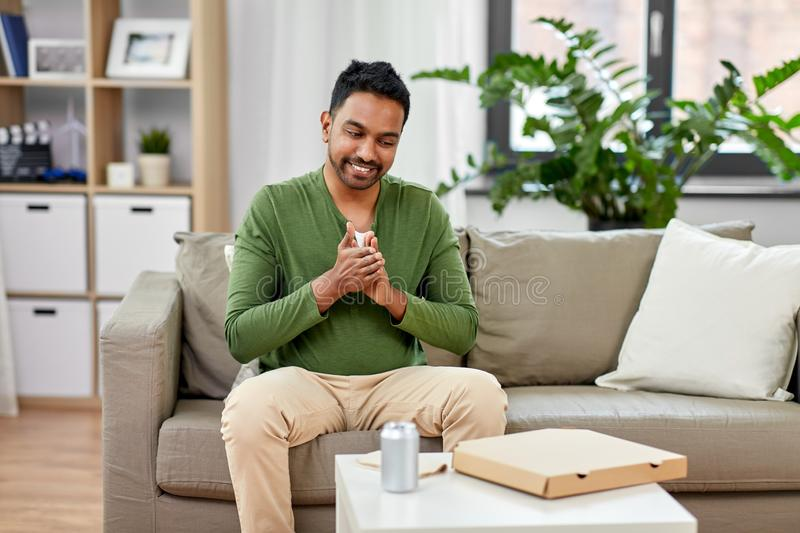 Indian man with takeaway pizza box at home. Food delivery, consumption and people concept - excited indian man rubbing hands and going to eat takeaway pizza at stock image