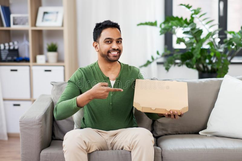 Indian man with box of takeaway pizza at home. Food delivery, consumption and people concept - smiling indian man with box of takeaway pizza at home royalty free stock photography