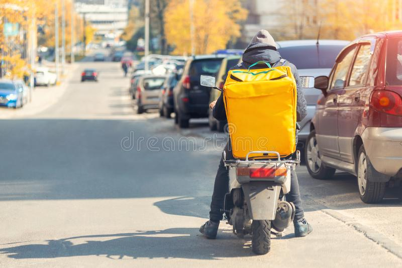Food delivery courier with big yellow backpack riding scooter on city street with traffic. Fast lunch takeaway delivery. Teenager royalty free stock photos