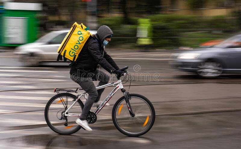 Food delivery courier - state of emergency due to coronavirus - Bucharest, Romania. Bucharest, Romania - March 23, 2020: A Glovo food delivery courier wearing stock photo