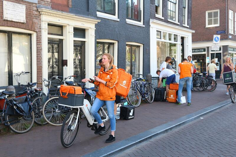Food delivery couriers. AMSTERDAM, NETHERLANDS - JULY 9, 2017: Uber Eats, Thuisbezorgd and Deliveroo food couriers wait in Amsterdam, Netherlands. Bicycle food stock photos