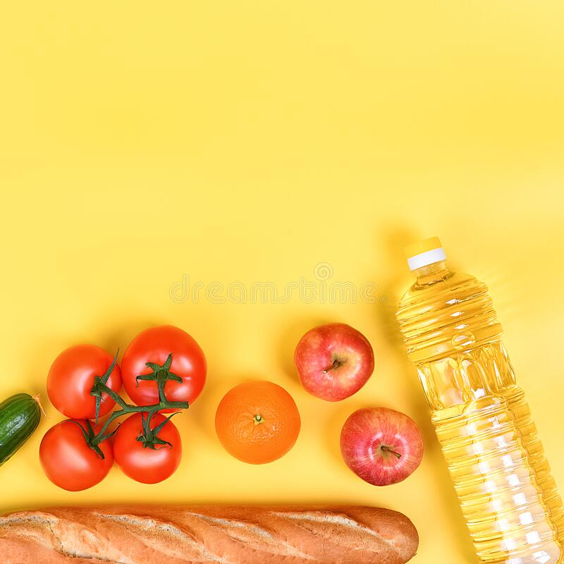 Food delivery, donation, food supply, copyspace. On a yellow background, buckwheat, pasta, sugar, peas, canned food, tomatoes,. Cucumber bread orange apple eggs stock photography