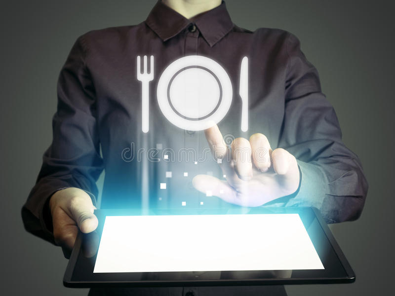 Food delivery. Image of a girl with tablet in her hands and food restaurant icon. She looking menus, ordering food delivery, rate restaurant with using online royalty free stock photography
