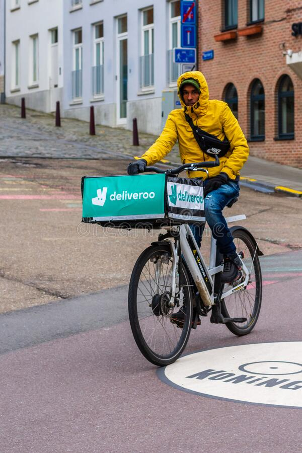 Food Delivery man riding bike on city road. Food Delivery man wearing yellow jacket riding zoomer bike on city road. The city buildings in the background. Rush royalty free stock photography