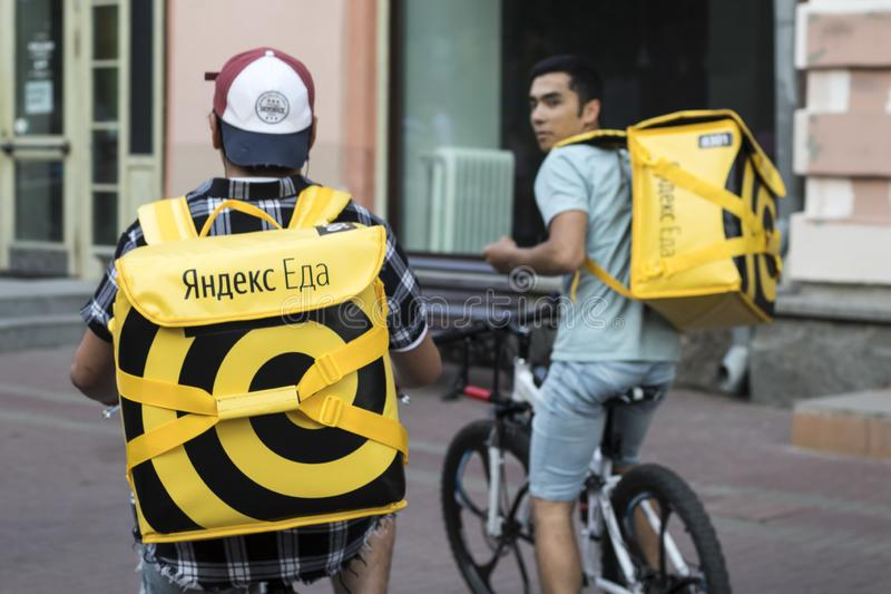 Food delivery in Moscow - courier in a hat with earflaps and a yellow jacket with inscription Yandex food and yellow backpack royalty free stock photo