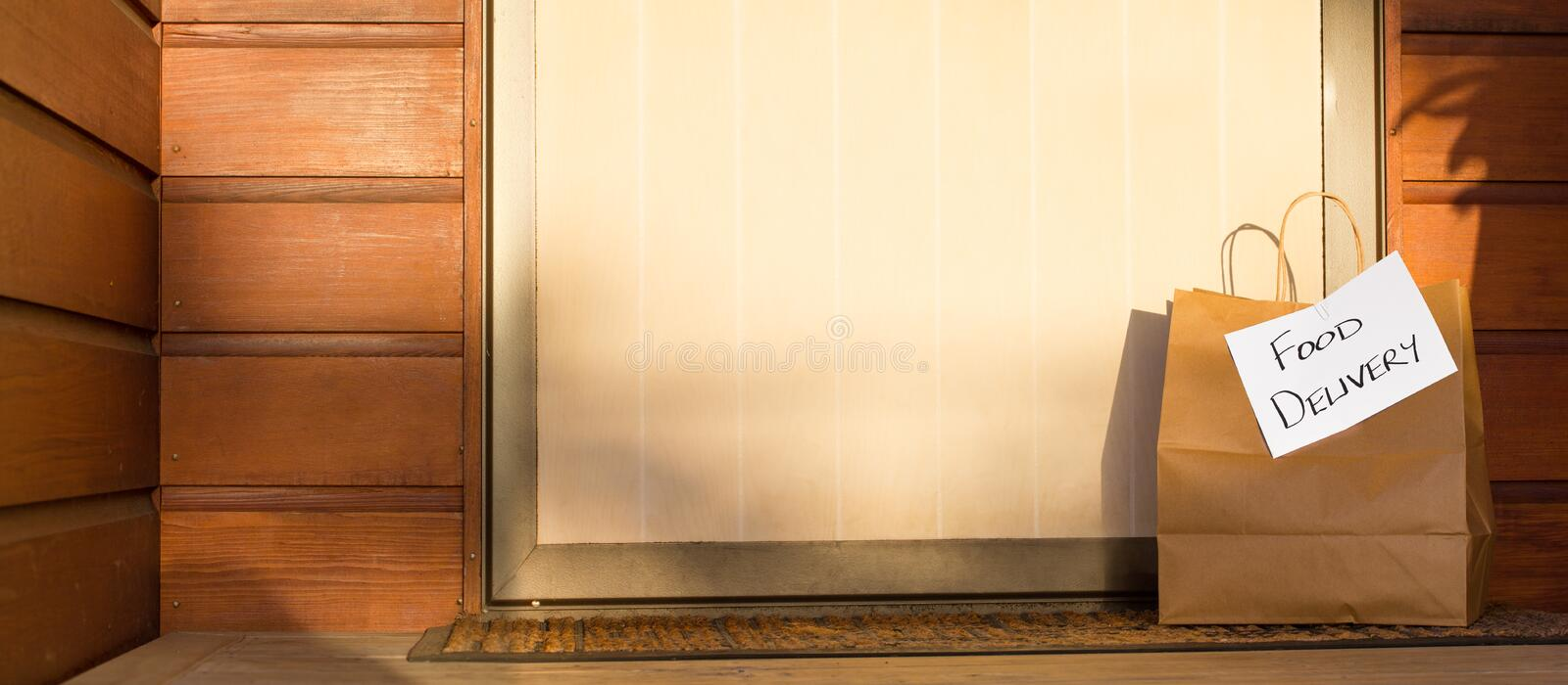 Food delivery in paper bag at door of home banner royalty free stock photos